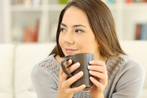 Pensive woman holding a coffee mug