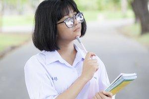 Schoolgirl standing holding a book.