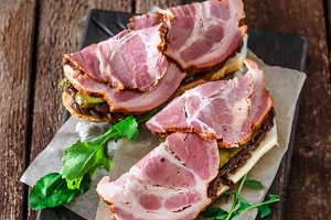 Sandwiches with smoked ham, onion jam, cucubbers and rocket salad on black board, rustic style