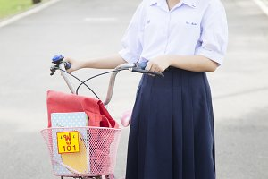 Schoolgirl. Stand and hold the bike