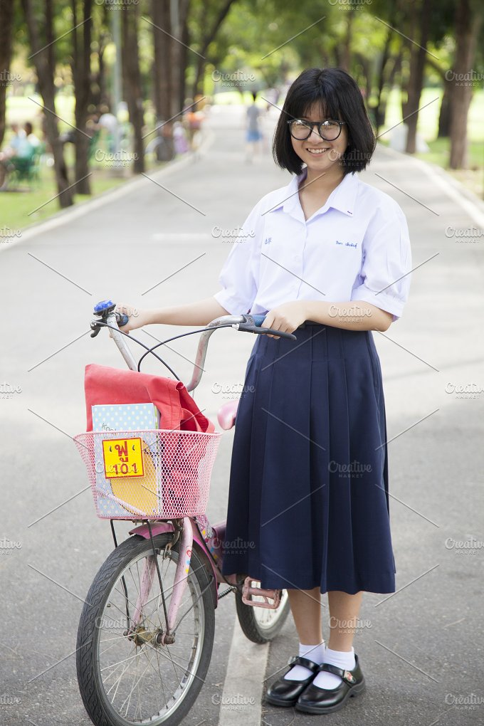 Schoolgirl. Stand and hold the bike - People