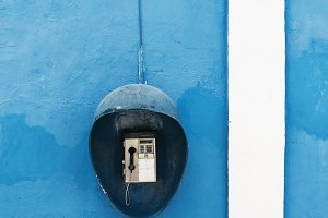Public phone on the blue wall.