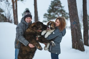 Happy couple with two dogs in winter forest. Lovely moments outdoor holidays