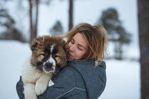 Portrait Girl with cute Caucasian Shepherd Dog in winter park