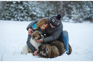 Happy moments with young romantic couple with two dogs at winter park