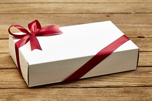 gift box with red bow on wood