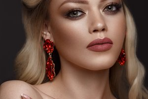 Beautiful blond girl with a golden crown, earrings and professional evening make-up. Beauty face.