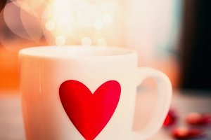 Mug with heart on table at bokeh