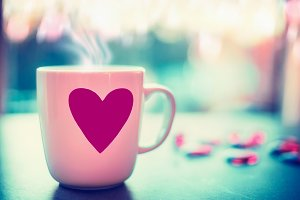Mug with pink heart on window sill