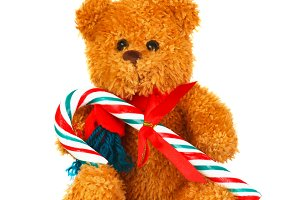 Brown teddy bear with a candy cane