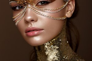 Beautiful girl in golden mask and bright evening make-up. Beauty face.