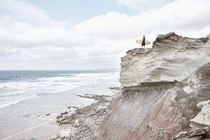 Surfer girl on cliff near ocean