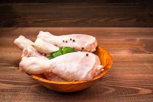 Raw chicken legs with bell pepper and herbs in a wooden plate on a wooden brown background.