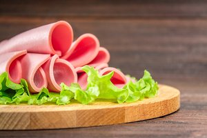 Sliced sausages with salad leaves on the wood background.