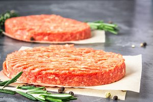 Raw burgers on parchment paper with tomatoes, chili peppers and rosemary. Grey marble background