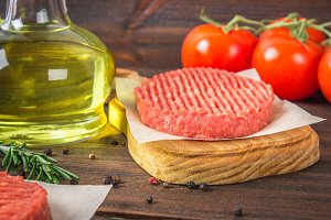 Raw burgers on parchment paper with rosemary and tomatoes. Wooden brown background