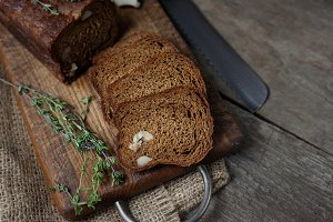 Black bread on wooden background.