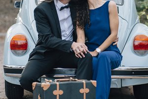 A young couple with a retro car with