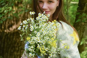 Young beautiful woman is standing in the forest with a bouquet of chamomiles