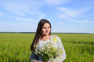 Young beautiful girl with a bouquet of chamomiles. A woman in a barley field