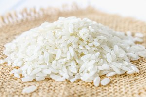 Grains of raw white rice on a white wooden table of boards. Ingredients for cooking.