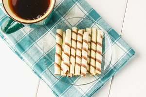 Striped wafer rolls, delicious chocolate snack on white wooden table.