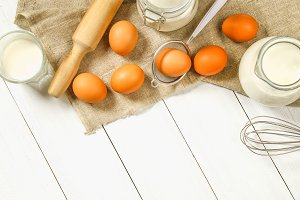 Raw brown chicken eggs, milk, sugar, flour, whisk, rolling pin on a white wooden table. Ingredients for cooking.