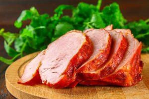 Sliced Roast Pork Loin on a brown wooden table with cilantro.