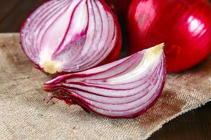 Fresh red onions and chopped slices on a wooden table.