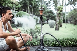 man smoking a hookah on vacation