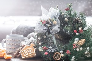 Christmas still life of trees and decorations, festive wreath on a background of knitted clothes and beautiful cups,