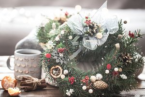Christmas still life of trees and decorations, festive wreath on a background of knitted clothes and beautiful cups