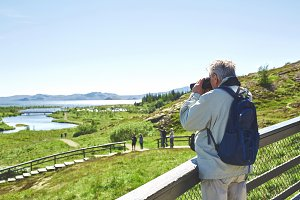 tourist walking and photographing in national park Thingvellir in Iceland