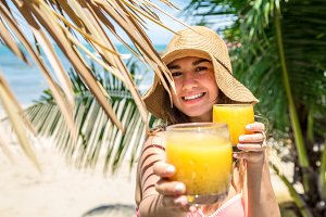 beautiful girl in a summer hat, with a fresh drink on the background of palm leaves on the beach, holiday concept