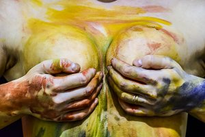 Chest of a girl with her nipples covered in her hands.