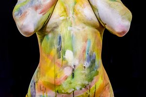 Chest of a girl with her nipples covered in her hands. A white young girl painted the body with paint