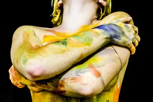 Body art. Drawing on the body. Beautiful girl with painted body watercolors. A white young girl painted the body with paint