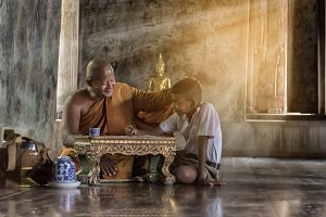 Thai monk are teaching a boy