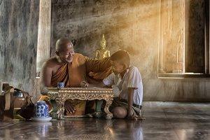 Thai monk are teaching a boy