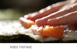Making sushi rolls with salmon