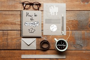 Notebook, coffee cup, glasses and pen on table. Business concept.
