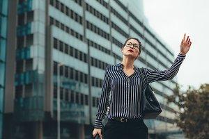 Female business executive hailing ta