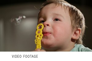 Two year old boy blowing soap bubble