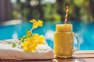 Mango smoothies on the background of the pool. Fruit smoothie - healthy eating concept. Close up of detox smoothie with mango