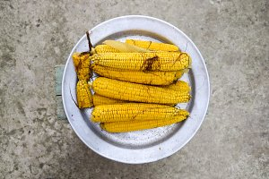 Boiled corn on an aluminum tray. Yellow boiled young corn, useful and tasty food