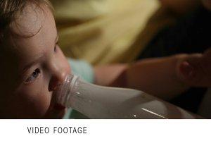 Boy drinks yogurt from a bottle.