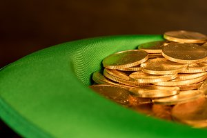 Pile of pure gold coins inside green hat St Patricks Day
