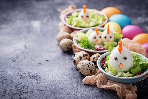 Salad with eggs in shape of chickens. Festive food.