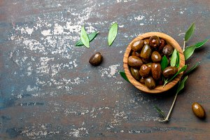 Bowl of olives an olive tree branch, dark background, top view copy space