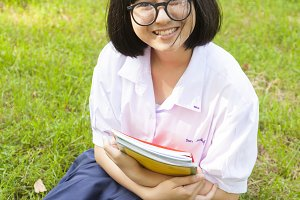 Schoolgirl holding books and smiling